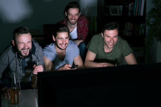 Gruppe von männern, die bier trinken und fußball im fernsehen schauen Kostenlose Fotos