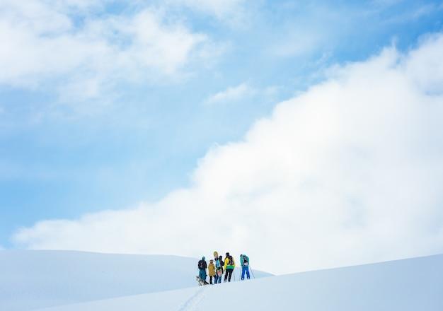 Gruppe von menschen, die in den bergen wandern, die im schnee unter dem schönen blauen himmel bedeckt sind Kostenlose Fotos