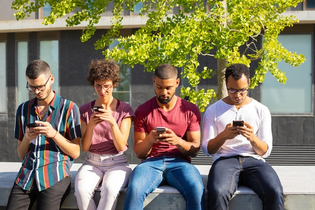 Gruppe von menschen konzentrierte sich auf ihre smartphones Kostenlose Fotos