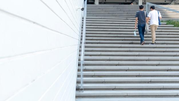 Gruppe von personen auf der rückseite gehen die außentreppentreppenlandschaft hinauf. Premium Fotos