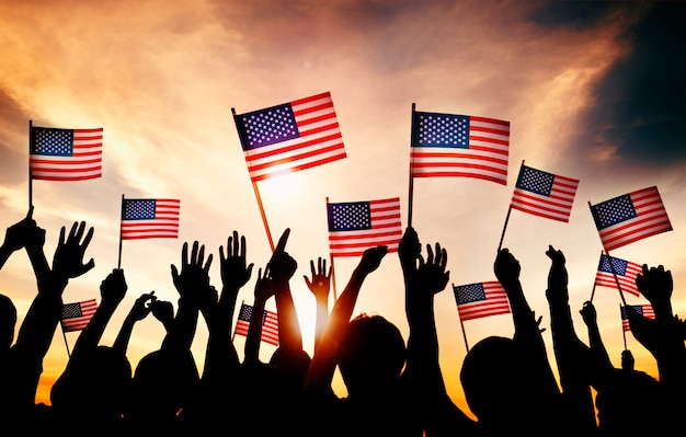 Gruppe von personen, die amerikanische flaggen in gegenlicht wellenartig bewegt Kostenlose Fotos