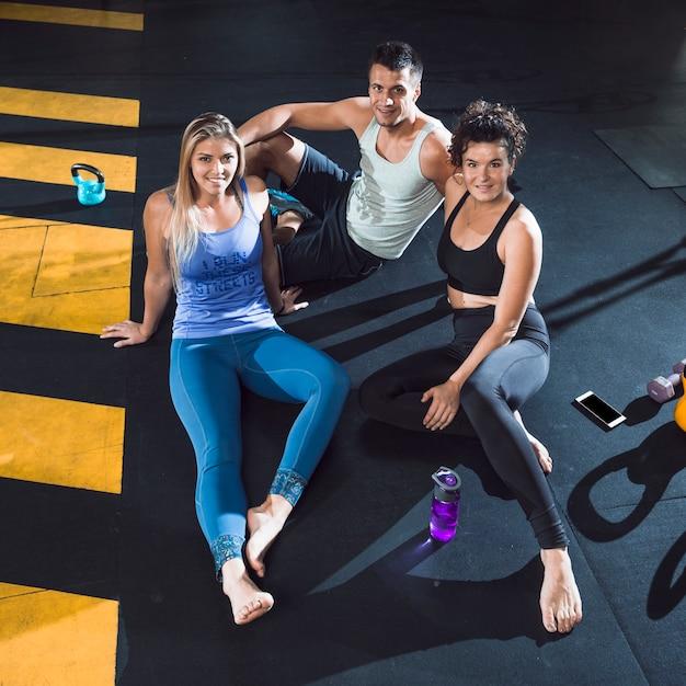 Gruppe von personen, die auf boden im fitness-club sitzt Kostenlose Fotos