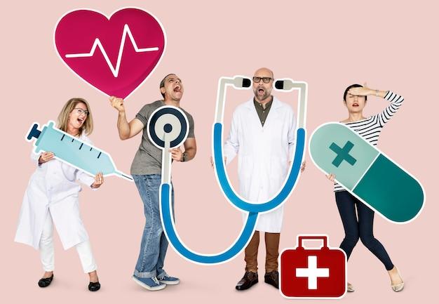 Gruppe von personen, die gesundheitspflegeikonen hält Premium Fotos