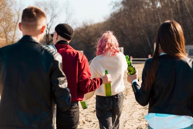 Gruppe von personen, die mit bierflaschen geht Kostenlose Fotos