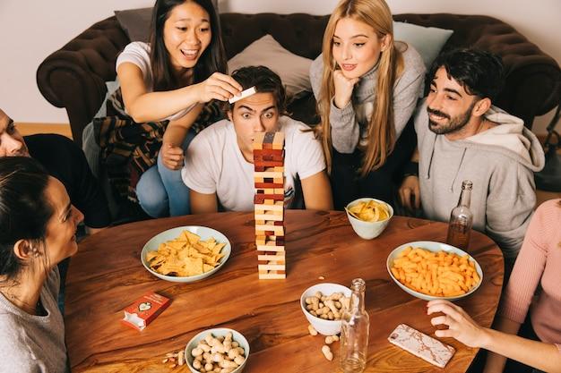 Gruppe von sechs glücklichen freunden, die tabletopspiel spielen Kostenlose Fotos