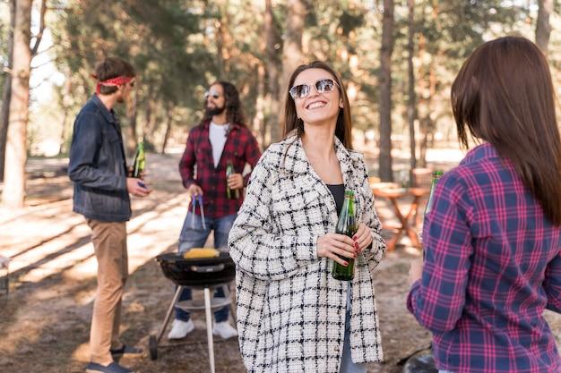 Gruppe von smiley-freunden, die bier über dem grill haben Kostenlose Fotos