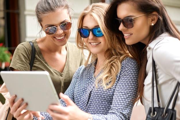 Gruppe von stilvollen frauen, die in der stadt genießen und ein digitales tablet verwenden Kostenlose Fotos