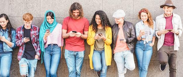 Gruppe von tausendjährigen freunden, die soziale geschichte auf smartphones beobachten. sucht der menschen nach neuen technologietrends Premium Fotos