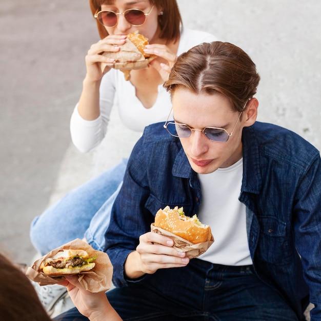 Gruppe von unholden, die burger im freien essen Kostenlose Fotos