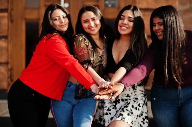 Gruppe von vier glücklichen und hübschen latinomädchen aus ecuador warf an der straße und am händchenhalten zusammen auf. Premium Fotos
