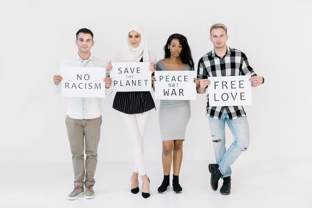 Gruppe von vier jungen gemischtrassigen menschen, die in die kamera schauen und plakate mit verschiedenen sozialen slogans halten, keinen krieg, freie liebe, die erde retten, keinen rassismus Premium Fotos