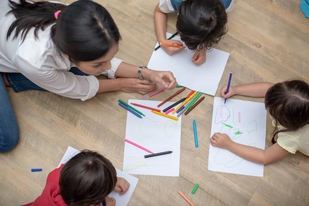 Gruppe vorschüler und lehrer, die auf papier in der kunstklasse zeichnen. Premium Fotos