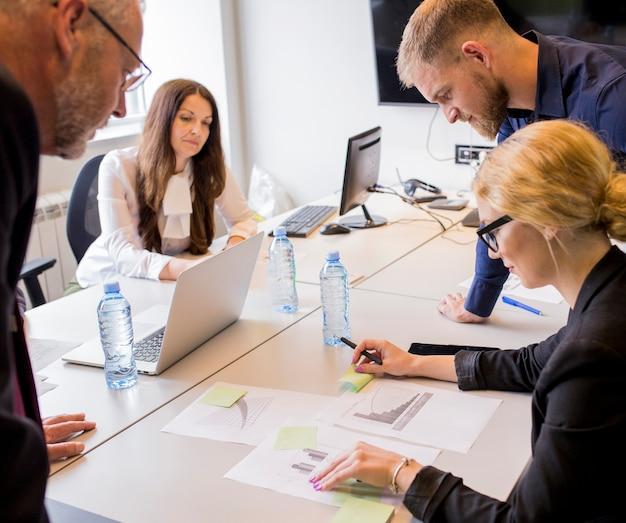 Gruppe wirtschaftler, die die unterschiedliche art des diagramms auf tabelle im büro analysieren Kostenlose Fotos