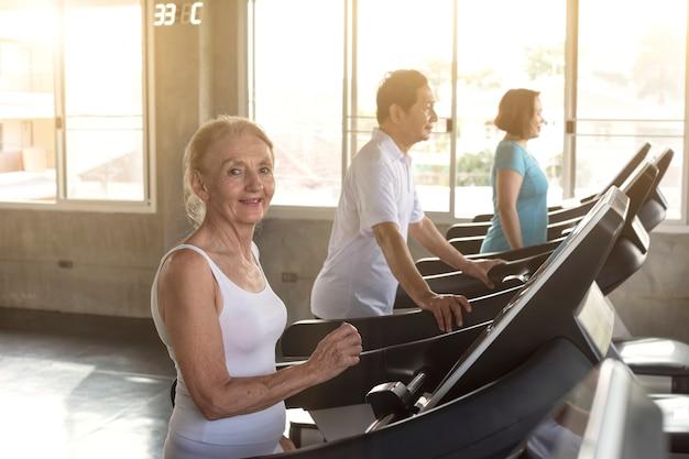 Gruppenfreund des älteren läufers an der turnhalleneignung lächelnd und glücklich. älterer gesunder lebensstil. Premium Fotos