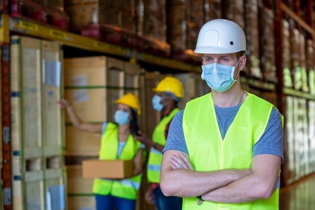 Gruppenlagerarbeiter, die schutzmaske tragen, die in der industriefabrik oder im lager arbeitet. Premium Fotos