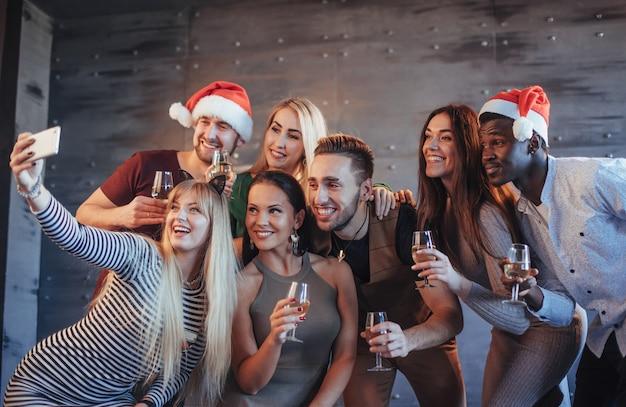 Gruppieren sie die schönen jungen leute, die selfie in der partei des neuen jahres, in den mädchen und in den jungen der besten freunde tun, die zusammen spaß haben und emotionale lebensstilleute aufwerfen. hüte santas und champagnergläser in ihren händen Premium Fotos