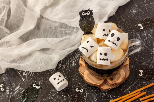 Gruselige gesichter (monster) von marshmallows in einer tasse kaffee für halloween Premium Fotos