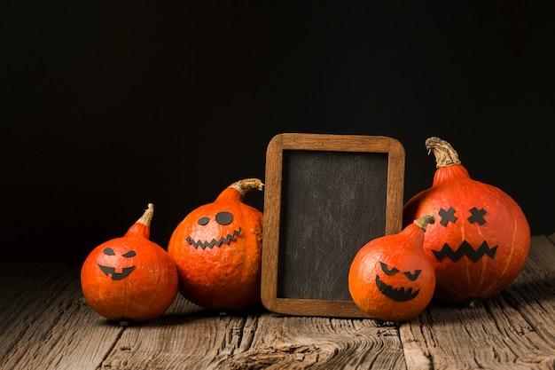 Gruselige halloween-kürbise mit modellrahmen Kostenlose Fotos