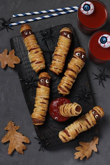 Gruselige wurstmumien, tomatensaft und sauce für die halloween-party auf schwarzem holzbrett. draufsicht Premium Fotos
