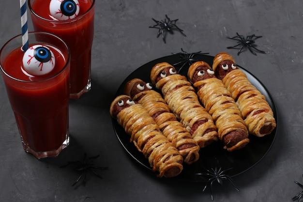 Gruselige wurstmumien und tomatensaft für halloween-party auf schwarzem teller. Premium Fotos