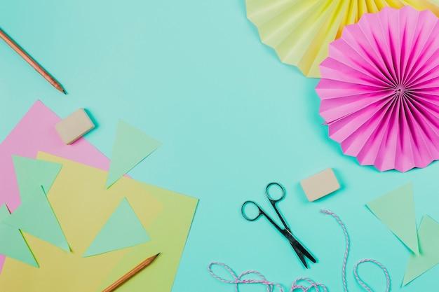 Gruß papier; bleistift; schere; radiergummi und kreisförmiges blumenpapier auf aquamarinem hintergrund Kostenlose Fotos