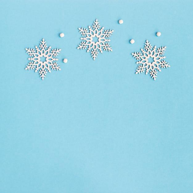 Grußkarte der frohen weihnachten und des guten rutsch ins neue jahr mit hölzernen schneeflocken auf blauem hintergrund Premium Fotos