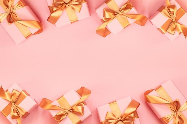 Grußkarte der frohen weihnachten und des guten rutsch ins neue jahr mit papiergeschenkbox, goldbandbogen auf einem rosa hintergrund. Premium Fotos