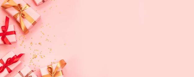 Grußkarte der frohen weihnachten und des guten rutsch ins neue jahr mit papiergeschenkbox, goldrotem bandbogen und funkelnkonfettis auf einem rosa hintergrund. Premium Fotos