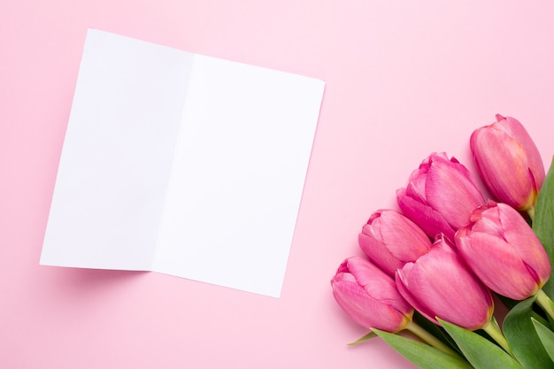 Grußkarte und rosa blumentulpen auf einer rosa oberfläche Premium Fotos