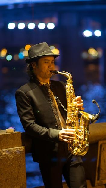 Guangzhou, china - 15. märz 2016: mann, der saxophon auf der straße am abend spielt Premium Fotos