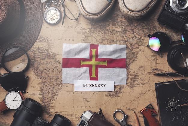 Guernsey-flagge zwischen dem zubehör des reisenden auf alter weinlese-karte. obenliegender schuss Premium Fotos
