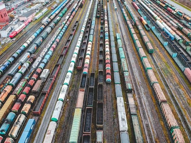 Güterzüge. vogelperspektive von bunten güterzügen auf dem bahnhof. wagen mit waren auf der eisenbahn. schwerindustrie. industrielle begriffsszene mit zügen. blick vom fliegenden drohne. Premium Fotos