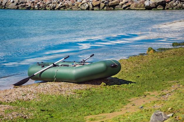 Gummiboot mit der fischereiausrüstung, die auf einem fluss nahe dem sandigen strand steht. Premium Fotos