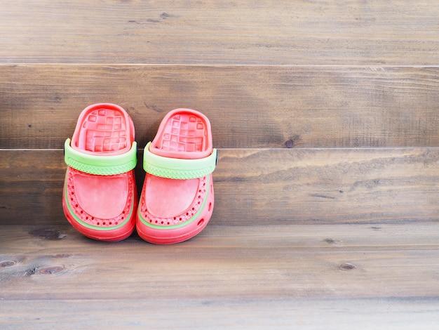 Gummisandalen der kinder auf holz Premium Fotos