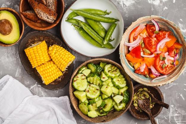 Gurkensalat, tomatensalat, mais und erbsen, draufsicht Premium Fotos