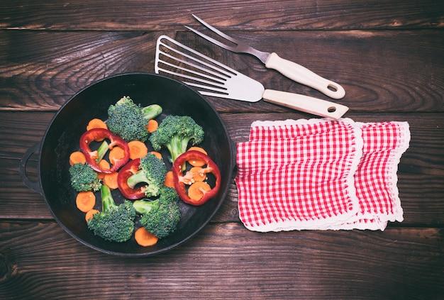 Gusseisenpfanne mit möhrenstücken, brokkoli Premium Fotos