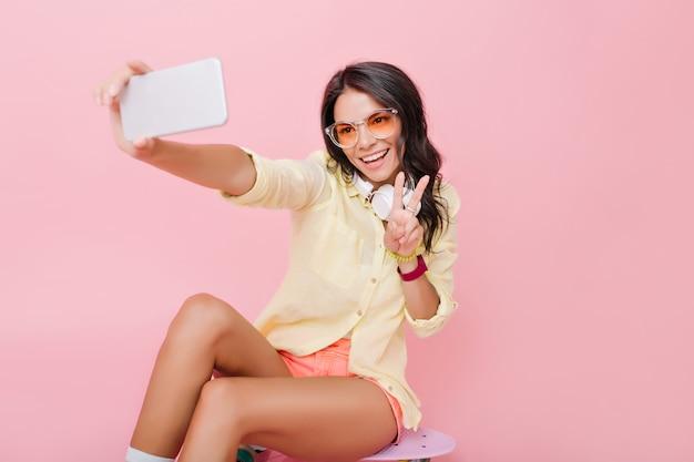 Gut aussehende europäische frau mit bronzebräune, die selfie auf smartphone macht. frohes liebenswertes mädchen in der gelben jacke, das foto von sich mit friedenszeichen macht. Kostenlose Fotos
