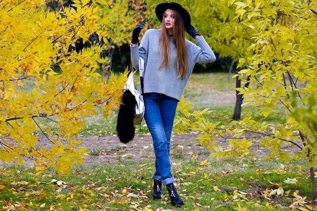 Gut aussehende frau mit langen haaren trägt jeans und handschuhe, die in sicherer haltung auf naturhintergrund stehen. foto im freien des hübschen weiblichen modells im trendigen grauen pullover, der im park am herbsttag geht. Kostenlose Fotos