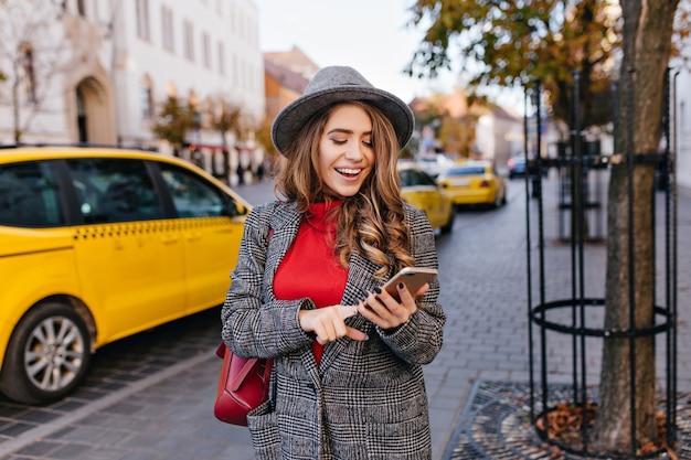 Gut aussehende geschäftsfrau, die eine nachricht beim gehen auf der straße sendet Kostenlose Fotos