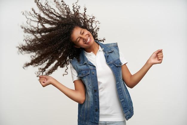 Gut aussehende glückliche dunkelhäutige frau, die mit ihrem langen lockigen haar spielt, während sie in freizeitkleidung auf weiß steht, breit lächelt und die augen geschlossen hält Kostenlose Fotos