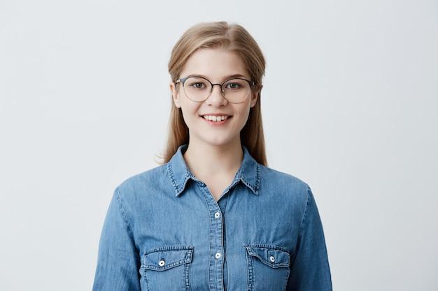 Gut aussehende kaukasische frau mit blonden glatten haaren, brille und jeanshemd, lächelt glücklich, hat gute laune nach erfolgreichem tag an der universität, froh und erfreut zu posieren Kostenlose Fotos