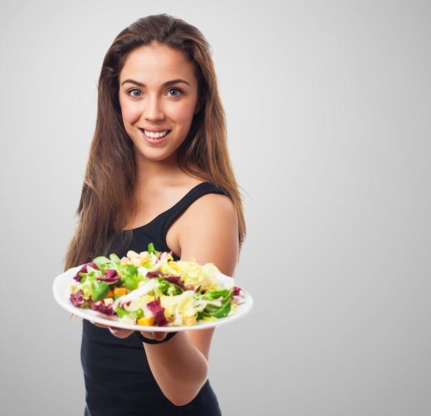 Gut aussehende modell einen teller mit salat hält Kostenlose Fotos