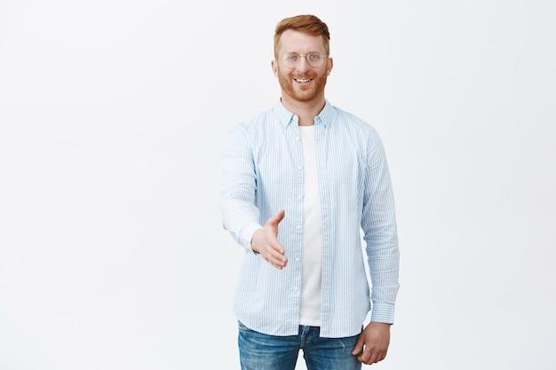 Gut aussehender freundlicher und charmanter rothaariger mann mit borsten in brille und hemd, die hände in handschlaggeste zu ziehend und glücklich lächelnd Kostenlose Fotos