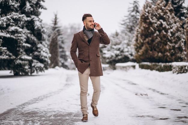 Gut aussehender mann, der am telefon in einem winterpark spricht Kostenlose Fotos
