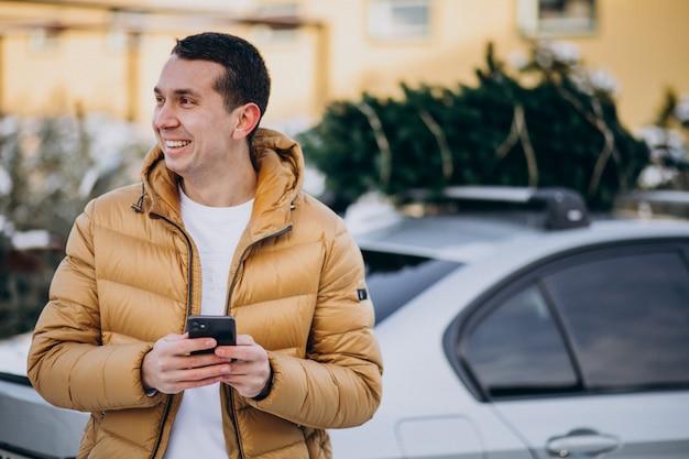 Gut aussehender mann, der am telefon mit dem auto mit weihnachtsbaum auf die oberseite spricht Kostenlose Fotos