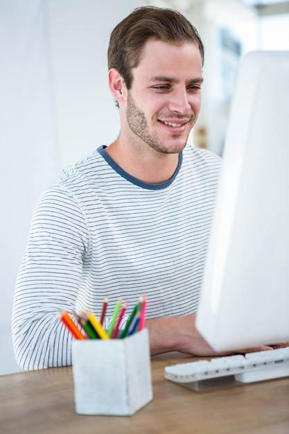 Gut aussehender mann, der an computer in einem hellen büro arbeitet Premium Fotos