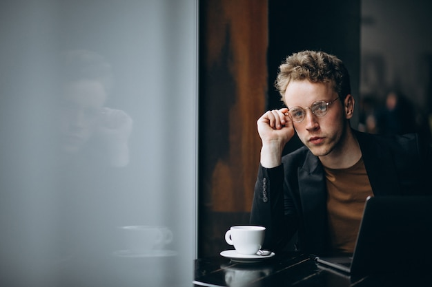 Gut aussehender mann, der an einem computer in einem café arbeitet und kaffee trinkt Kostenlose Fotos