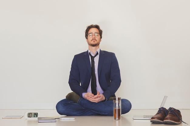 Gut aussehender mann, der auf boden meditiert Kostenlose Fotos