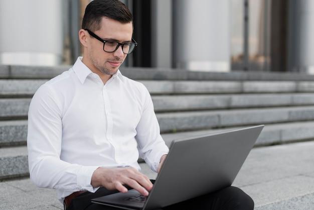 Gut aussehender mann, der auf laptop schaut Kostenlose Fotos