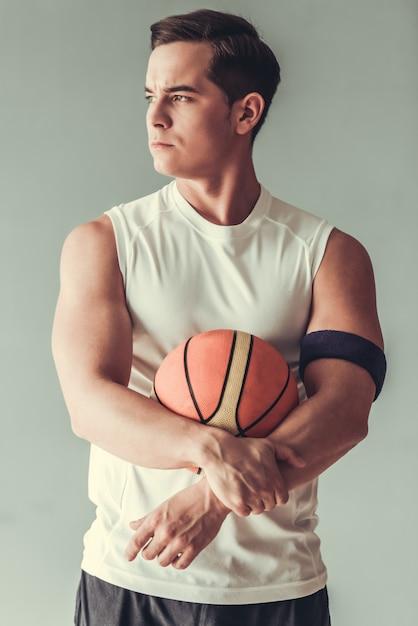 Gut aussehender mann, der basketballball hält Premium Fotos